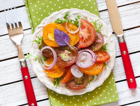 cebolla roja: Ensalada de tomate fresco con cebolla roja, albahaca y cia semillas de cerca.