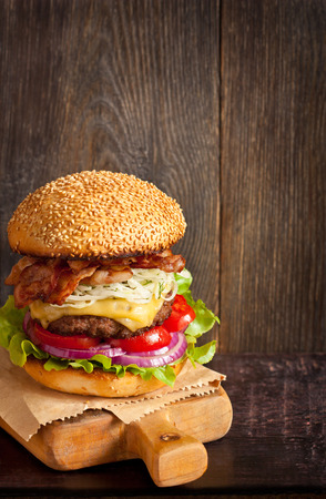 sesame seed bun: Big delicious cheeseburger stacked high with a bacon, beef patty, coleslaw, cheese, lettuce, red onion and tomato on sesame seed bun served  on wooden cutting board. Stock Photo