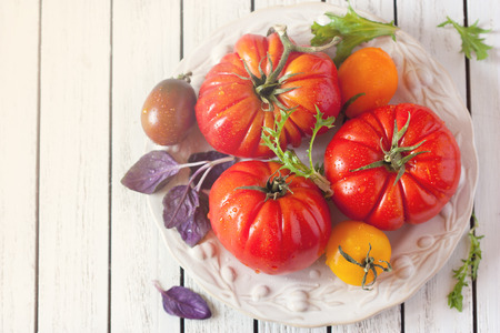 heirloom: Fresh colorful heirloom tomatoes and herbs for cooking salad. Stock Photo