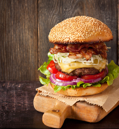sesame seed bun: Big delicious cheeseburger stacked high with a bacon, beef patty, coleslaw, cheese, lettuce, red onion and tomato on sesame seed bun served on wooden cutting board.