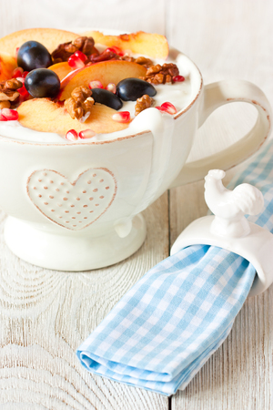 napkin ring: Homemade yogurt with fresh fruit in big bowl for healthy breakfast closeup. Stock Photo