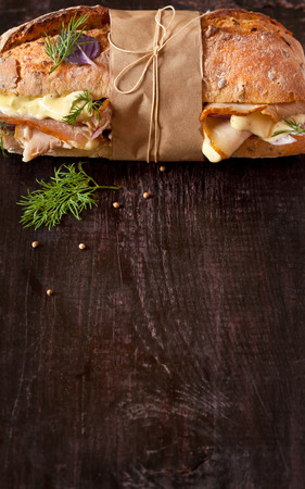 delicatessen: Delicious meat sandwich wrapped in paper with kitchen twine on wood background with copy space for text.