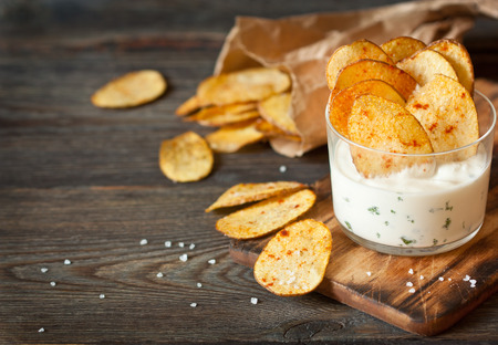 chips: Homemade potato chips and spicy dip served in glass.