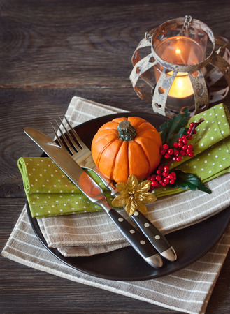 background settings: Festive autumn place settings with pumpkin, berries and candle on wooden background.