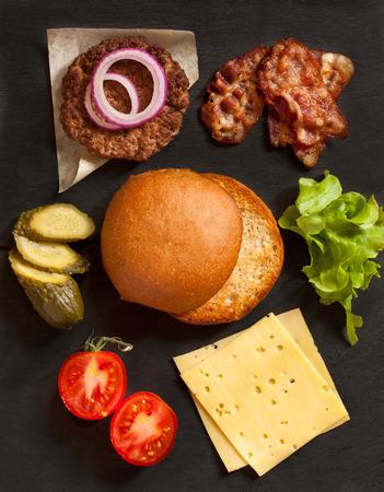 HAMBURGUESA: Los ingredientes frescos para la construcción de la hamburguesa sobre fondo negro.