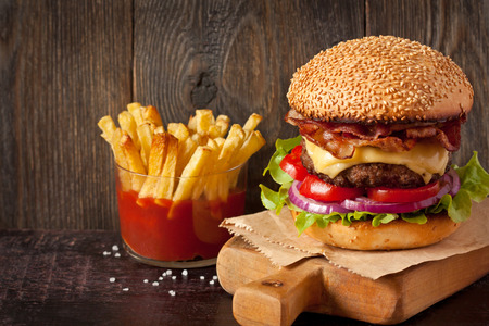 sesame seed bun: Big delicious cheeseburger stacked high with a bacon, beef patty, cheese, lettuce, red onion and tomato on sesame seed bun served  on wooden cutting board and fried potatoes with sauce.