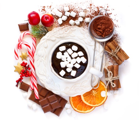 chocolate candy: Cup of creamy hot chocolate with marshmallows surrounded food ingredients and some christmas decoration on white background with place for text.