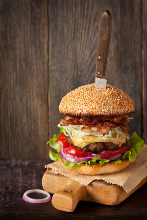 sesame seed bun: Big delicious cheeseburger stacked high with a bacon, beef patty, coleslaw, cheese, lettuce, red onion and tomato on sesame seed bun served old knife on wooden cutting board.