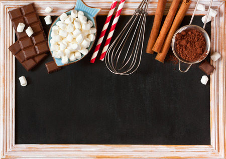 sweet: Hot chocolate mix on old chalk blackboard. Sweet marshmallow, chocolate bars, sugar, cocoa powder, cinnamon, and whisk for cooking winter holiday drink.