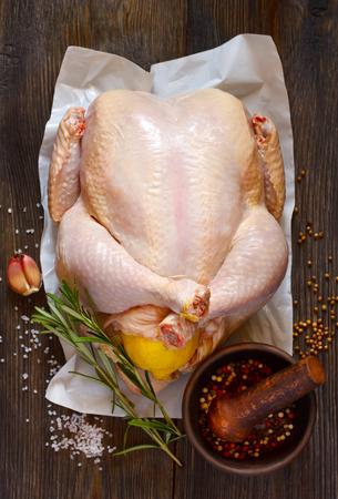 carne de pollo: pollo entero relleno de limón crudo fresco y especias para cocinar sobre tabla de madera. Vista superior.