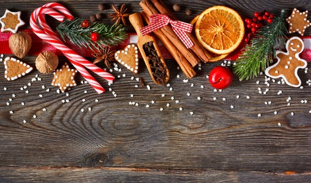 table decoration: Christmas border. Gingerbread cookies, spices and decorations on wooden background.