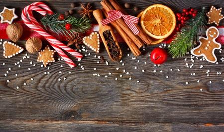 decoracion mesas: Frontera de la Navidad. Galletas de jengibre, las especias y las decoraciones en el fondo de madera.