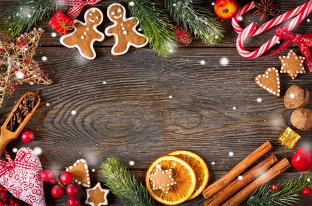 gingerbread: Christmas frame. Gingerbread cookies, spices and decorations on wooden background.