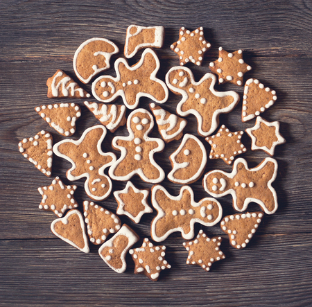 Domestic Christmas gingerbread cookies on old wooden background.
