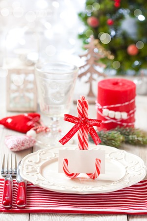 my name is: Christmas table place setting. Elegant empty plate, cutlery, napkin and blank name card on candy cane stand.