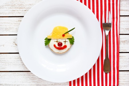 food dish: Funny clown two cheese crackers for children breakfast.