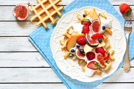 Fresh homemade waffles with berries and whipped cream. Stock Photo