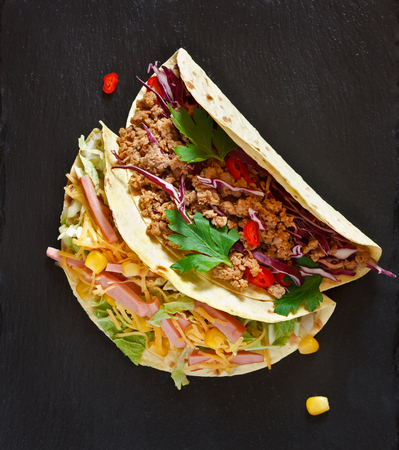 taco tortilla: Fresh delisious mexican tacos on black. Street food. Stock Photo