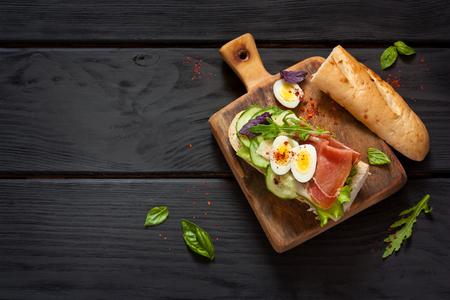 Fresh egg ham sandwich on dark board.