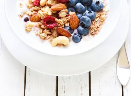 Homemade granola with fruit nuts and fresh yogurt.