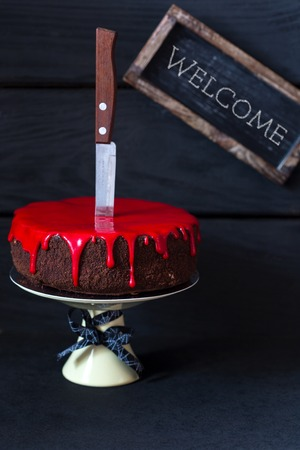 cakestand: Bleeding monster cake with knife on cakestand and welcome tag.