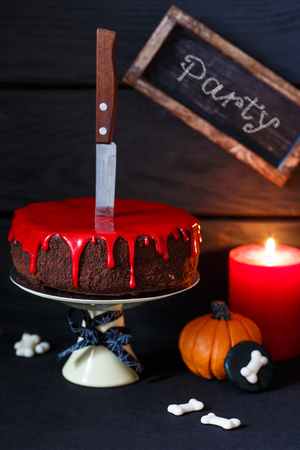 cakestand: Bleeding monster cake with knife on cakestand, pumpkin and candle.