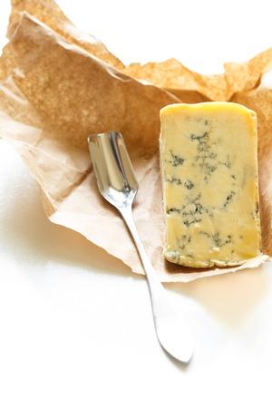 stilton: Slice of blue Stilton cheese and stilton spoon on a white background