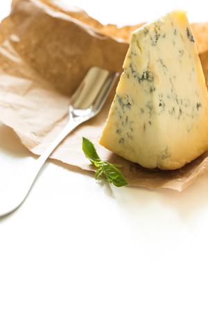 stilton: Slice of blue Stilton cheese and stilton spoon on a white background.