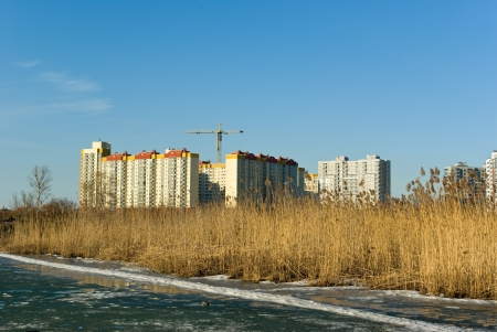 Under construction modern apartment buildings on lake bank in spring (Saint-Petersburg. Russia)