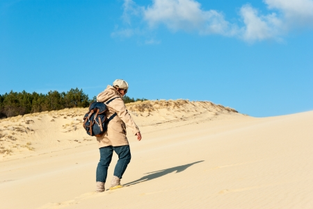 Young woman climbing on the Great dune of Pyla