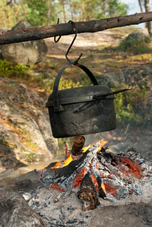 Travelling cooking - kettle over camping fire Stock Photo
