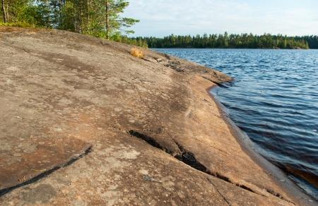 Granite rock coastline of forest lake, Leningrad Region, Russia