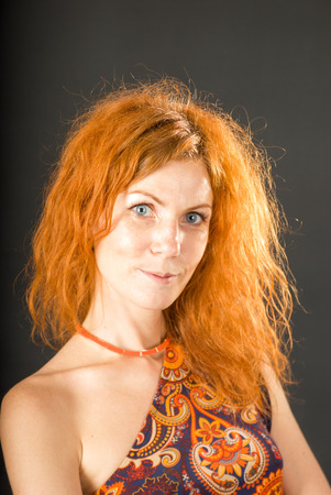 Portrait of smiling young woman with red hair on black background