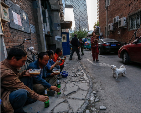 outsiders: migrant workers eating beside road