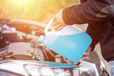 man refills windshield wiper water on a car