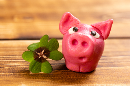 green shamrock with lucky pig on a wood background sign of happiness
