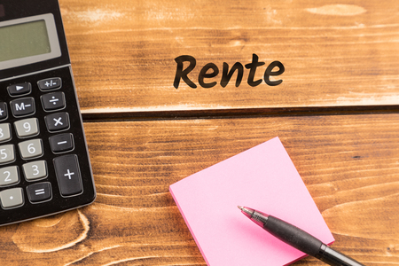 business desk with paper, pen and calculator with german text rente, in english pension Banco de Imagens