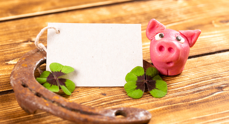 horseshoe with green shamrock and lucky pig sign for luck for st patricks day on a wooden background