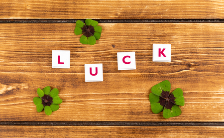 text luck on a wooden background with green lucky clover
