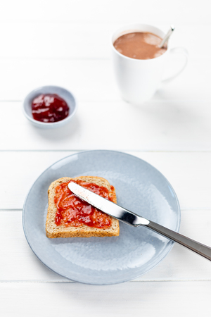 toast with strawberry jam on a blue plate and cup of cacao on a white wooden background Stockfoto