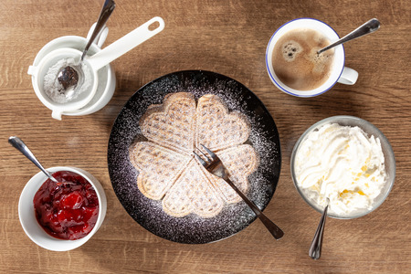 świeży wafel na czarnym talerzu z drewnianym tłem z kawą