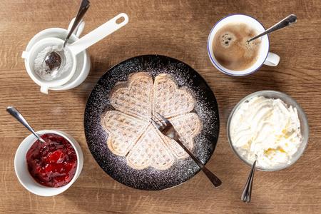 frische Waffel auf einem schwarzen Teller mit Holzuntergrund mit Kaffee
