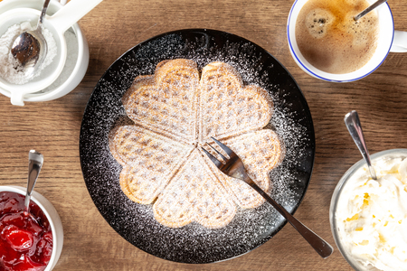 fresh waffle on a black plate with wooden background with coffee Standard-Bild