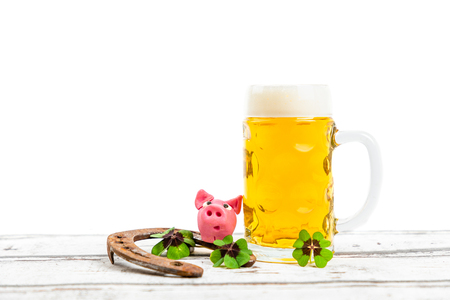 beer with pink pig, shamrock and horseshoe for st patricks day and copy space