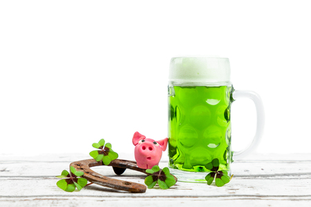 green beer glass with pink pig, shamrock and horseshoe for st patricks day