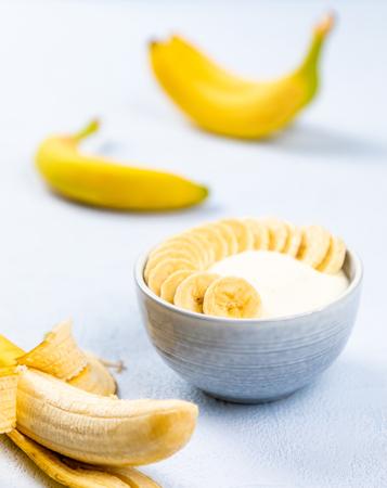 cream dessert with banana fruit in a bowl on blue background Reklamní fotografie
