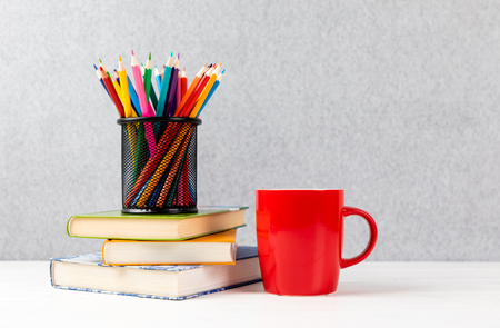 books, colorful pencils and red cup on a desk with gray background and copyspace