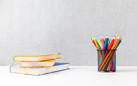 books and colorful pencils on a desk with gray background and copyspace