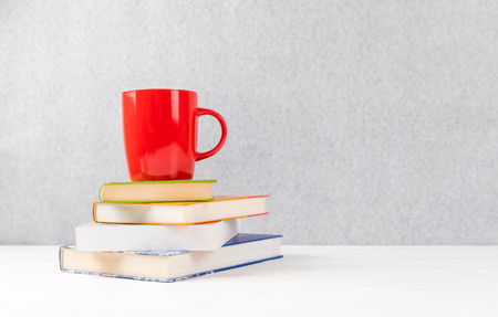 books with red cup on a table with gray background and copyspace