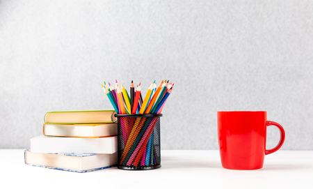 colorful pencils, books and red cup on a desk with gray background and copyspace